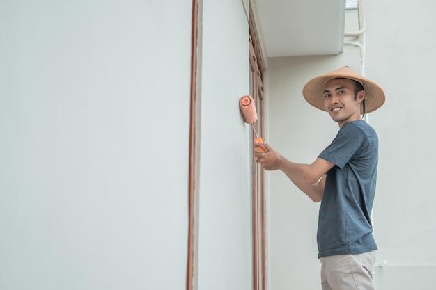 Un peintre avec un chapeau peint à l'aide d'un rouleau à peinture sur une construction de bâtiment