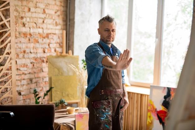 Peintre créatif en vêtements de travail couvrant une partie de la peinture avec la main tout en se tenant à une certaine distance devant le chevalet