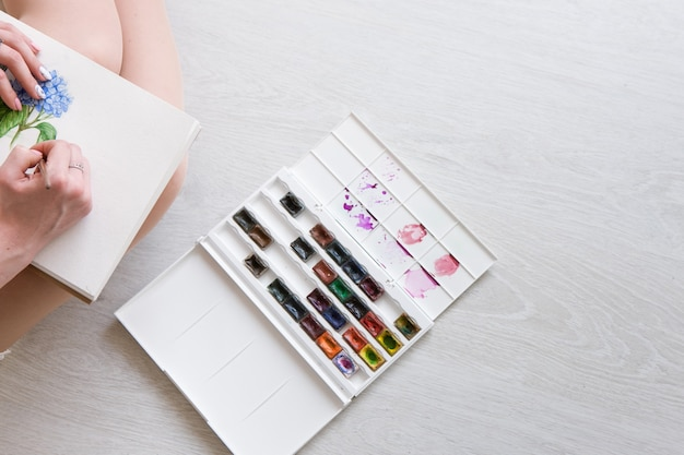 Le peintre dessine un croquis de fleur à l'aquarelle. oeuvre colorée de bouquet sur la vue de dessus de papier blanc. peinture d'artiste avec palette et pinceau.