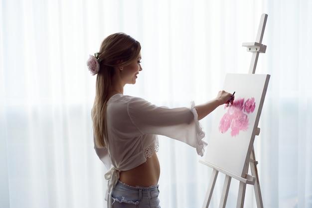 Peintre enceinte femme dessin en art studio à l'aide de chevalet. portrait d'une jeune femme enceinte peignant avec des peintures à l'huile sur toile blanche, portrait vue de côté