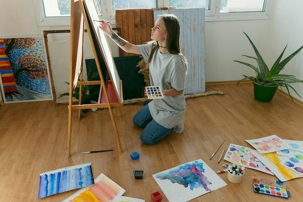 Peintre femme assise sur le sol