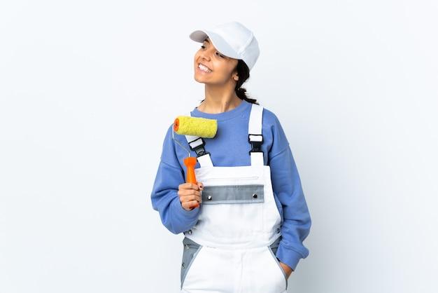 Peintre femme sur mur blanc isolé à côté