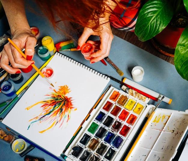 Le peintre de femme peint des peintures colorées sur la feuille blanche