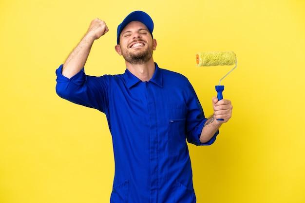 Peintre homme brésilien isolé sur fond jaune célébrant une victoire