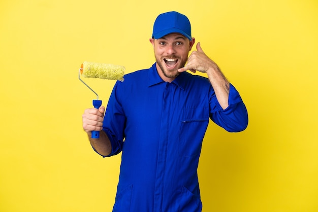 Peintre homme brésilien isolé sur fond jaune faisant un geste de téléphone. rappelle-moi signe
