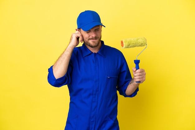 Peintre homme brésilien isolé sur fond jaune frustré et couvrant les oreilles