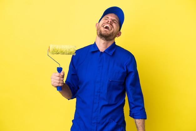 Peintre homme brésilien isolé sur fond jaune en riant