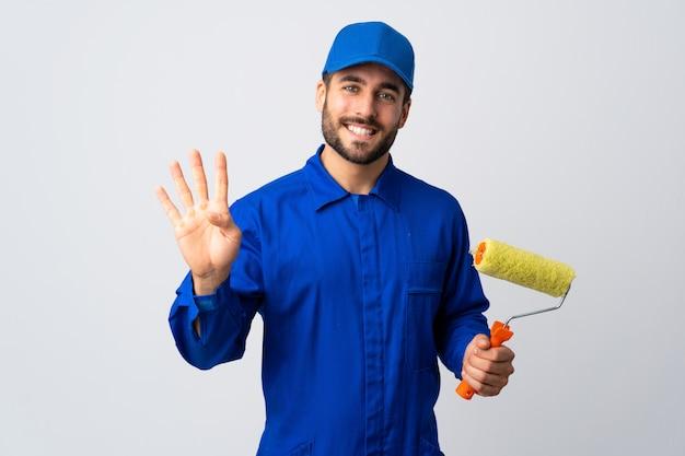 Peintre homme tenant un rouleau à peinture isolé sur mur blanc heureux et en comptant quatre avec les doigts