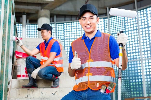 Peintre indonésien asiatique peindre avec un pinceau, un rouleau à peinture, de la couleur et des outils dans des bottes en caoutchouc ou des bottes en caoutchouc et des gants de protection les murs d'une tour ou d'un chantier de construction