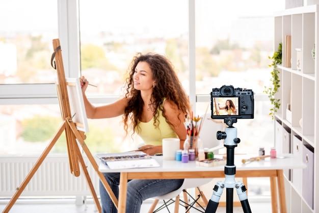 Peintre de jolie fille faisant une nouvelle photo assise en atelier