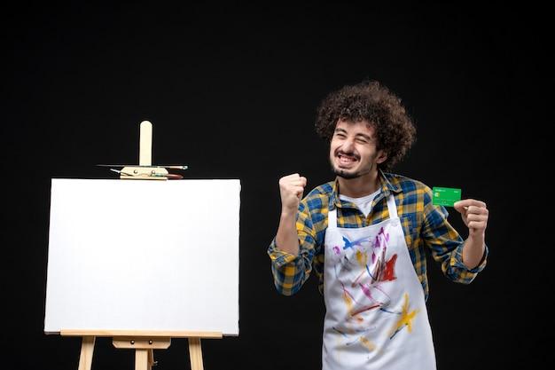 Peintre mâle vue de face tenant une carte bancaire verte se réjouissant sur un mur noir