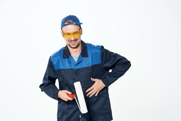 Peintre masculin construisant la réparation uniforme dans la maison