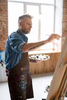 Peintre occupé en tablier et chemise en jean travaillant sur une nouvelle peinture en se tenant debout devant un chevalet en studio