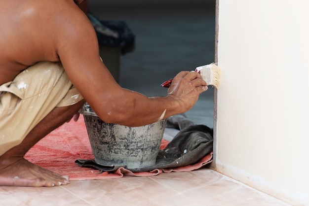 Peintre peignant le mur avec un seau de brosse et de peinture noire. concept d'architecture et de génie civil