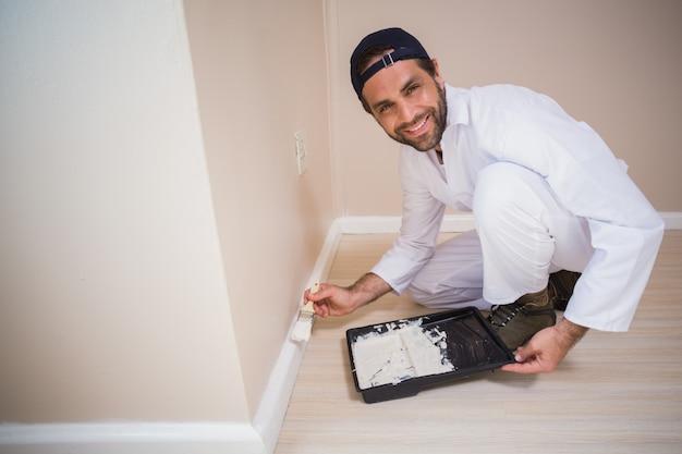 Peintre peignant les murs blanc
