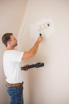 Peintre peignant les murs en blanc
