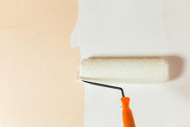 Peintre peignant les murs blancs dans la maison