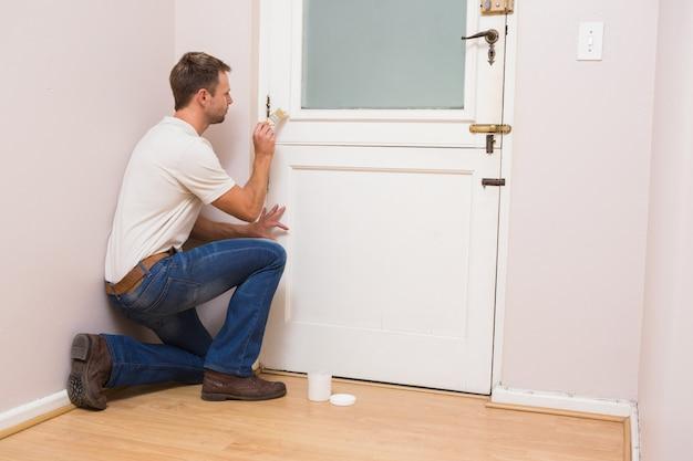 Peintre peignant la porte en blanc dans une nouvelle maison