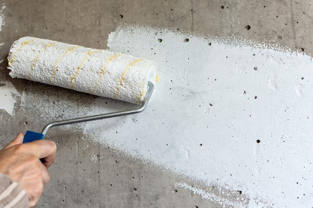 Un peintre peint un mur de béton avec de la peinture blanche, une main masculine avec un rouleau à peinture pour peindre un mur