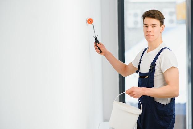 Le peintre peint un mur dans une pièce avec un rouleau.