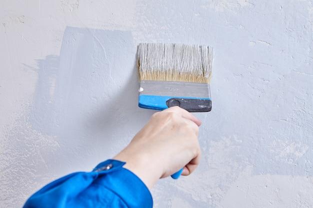 Peintre peint le mur avec un pinceau.