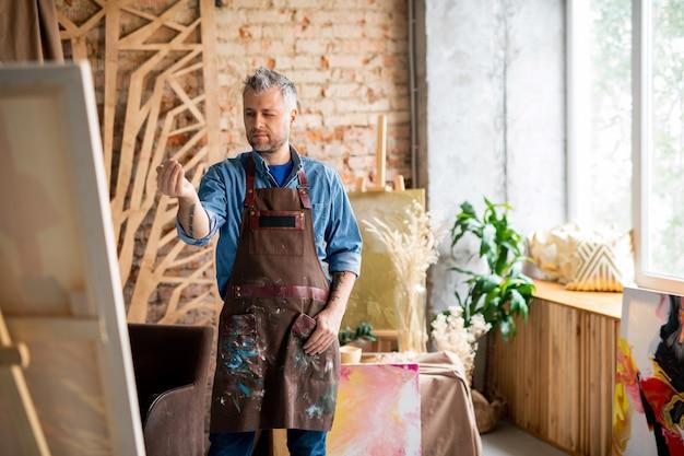 Peintre professionnel en tenue de travail debout devant un chevalet avec un œil fermé et déterminant le centre de la peinture