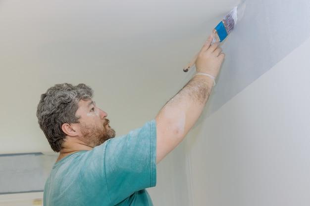 Peintre professionnel utilisant un pinceau pour appliquer de la peinture sur le mur