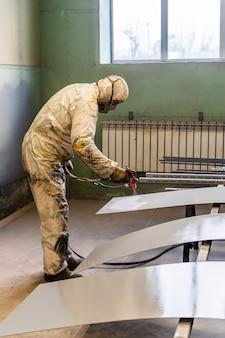 Le peintre en salopette de protection travaille dans l'atelier de peinture. photo prise à l'usine