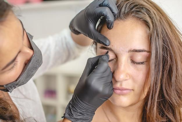 Le peintre de sourcils de maître de beauté peint les sourcils en les colorant avec du henné