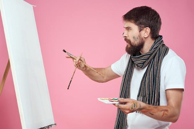 Peintre tenant la palette dessin art chevalet passe-temps créativité fond rose. photo de haute qualité