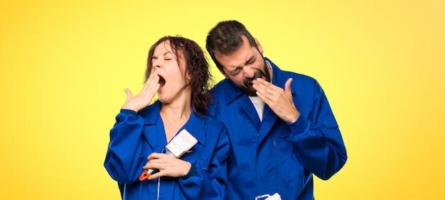 Les peintres bâillent et se couvrent la bouche avec la main. expression endormie sur fond coloré