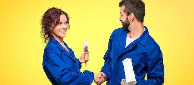 Peintres serrant la main pour avoir conclu une bonne affaire sur un fond coloré