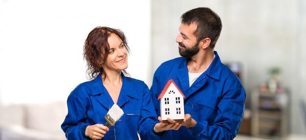 Peintres tenant une petite maison dans la maison