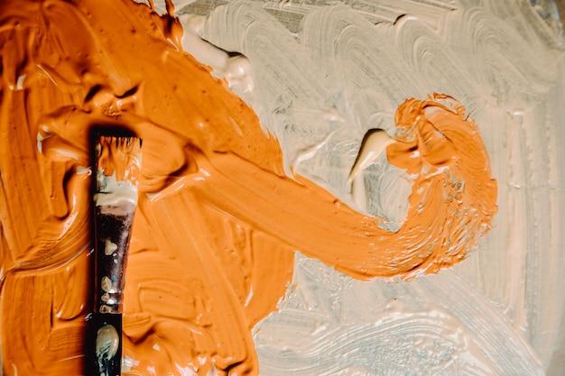Peinture abstraite acrylique et aquarelle. fond de toile avec un pinceau, couleur orange et blanche