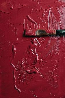 Peinture abstraite acrylique et aquarelle. fond de toile avec un pinceau, couleur rouge foncé