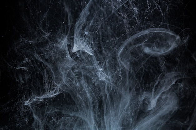 Peinture acrylique abstraite tourbillonne dans l'eau sur l'espace noir
