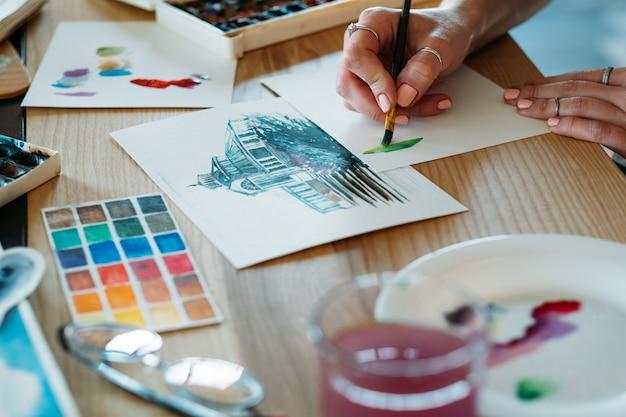 La peinture à l'aquarelle. artiste au travail. peintre faisant des coups de pinceau de mélange de couleurs. brouillon et fournitures de palette autour.