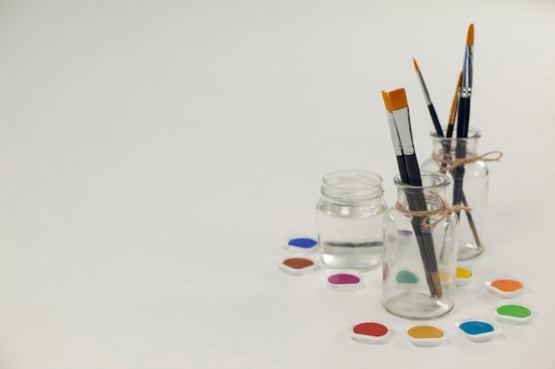 Peinture aquarelle et pinceaux dans des pots contre une surface blanche