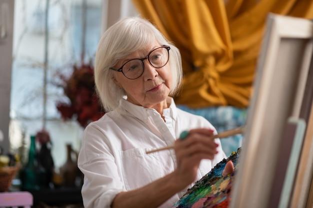 Peinture en atelier. femme âgée aux yeux sombres, peinture en atelier se sentant bien et inspirée