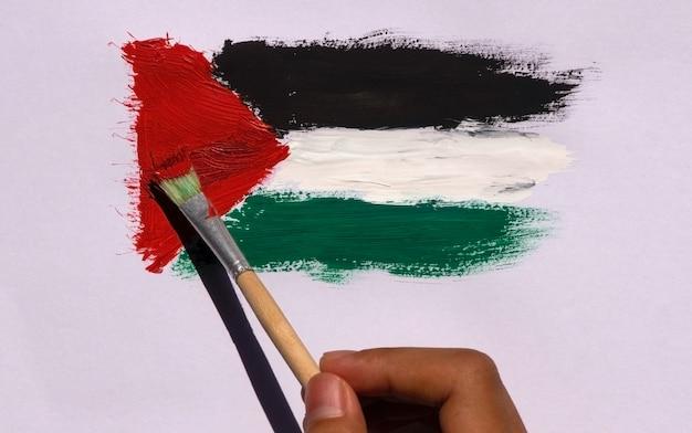 Peinture au pinceau du drapeau de la palestine sur un fond de papier blanc, mise au point sélectionnée.
