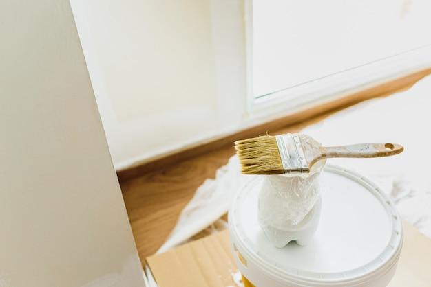 Peinture blanche sans émission de gaz sur un seau de peinture plastique écologique pour décorer la maison.