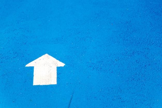 Peinture blanche en symbole de flèche de direction vers l'avant sur fond de route en béton bleu
