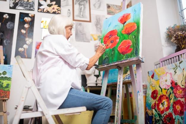 Peinture de coquelicots rouges. artiste talentueux âgé aux cheveux gris portant des jeans peignant de beaux coquelicots rouges