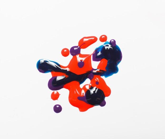 Peinture créative, art moderne abstrait. texture brillante de vernis à ongles de couleur rouge, bleu et violet barbouillé isolé sur fond blanc