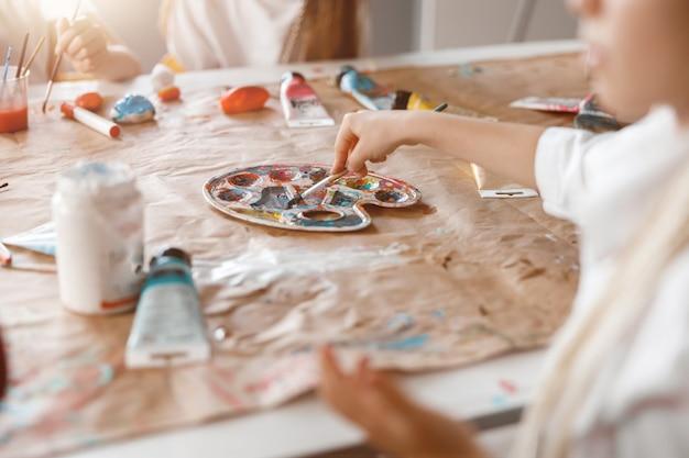 Peinture d'écolière sur papier avec des peintures colorées