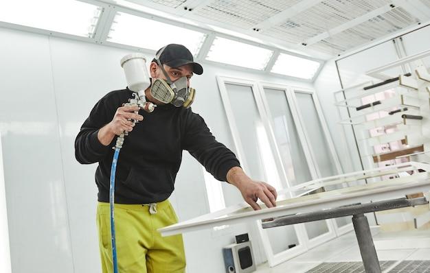 Peinture faite homme droit dans un masque respiratoire peignant des planches de bois à l'atelier