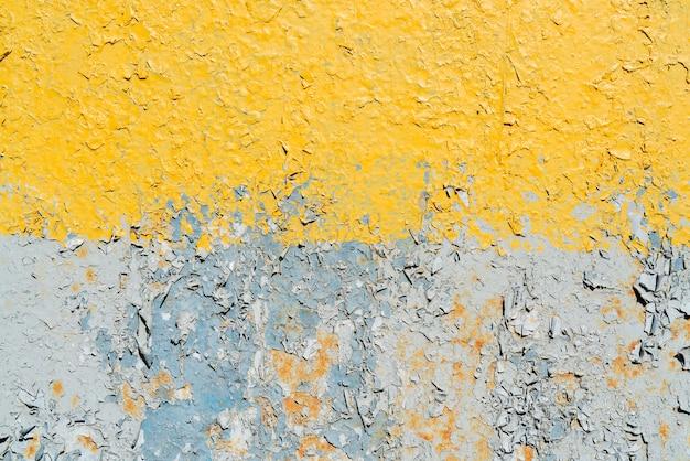 Peinture fissurée jaune et gris sur une surface métallique.
