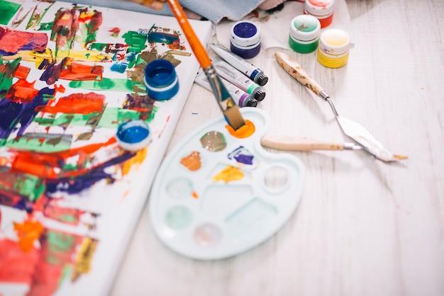 Peinture à la gouache avec palette au sol