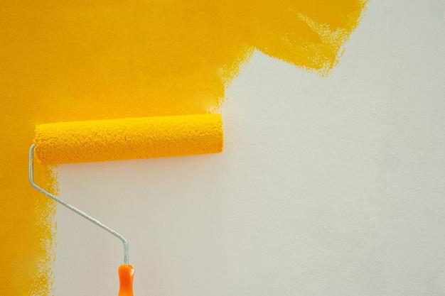 Peinture jaune avec un rouleau sur le mur diy par vous-même