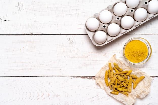 Peinture des œufs de pâques avec des colorants écologiques naturels, des colorants au curcuma, des œufs de poule sur une table blanche en bois.
